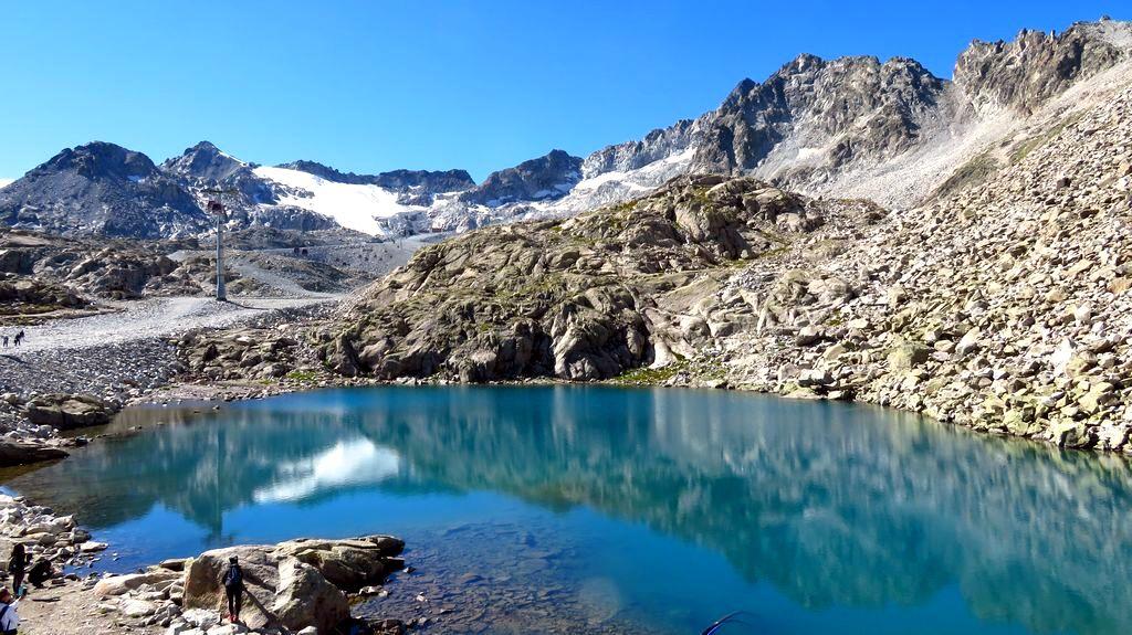 Trekking w Alpach grupa Adamello Presanella. Widok na Cima Presena i lodowiec Presena z nad Lago Monticello